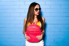 Belle jeune fille sexy posant et souriant près du fond bleu de mur dans le maillot de bain jaune, lunettes de soleil, sac à dos r Photos libres de droits