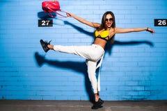 Belle jeune fille sexy posant et souriant près du fond bleu de mur dans le maillot de bain jaune, lunettes de soleil, sac à dos r Images libres de droits