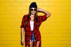 Belle jeune fille sexy posant et souriant près du fond jaune de mur dans des lunettes de soleil, chemise de plaid rouge, shorts,  Image stock
