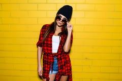 Belle jeune fille sexy posant et souriant près du fond jaune de mur dans des lunettes de soleil, chemise de plaid rouge, shorts,  Photo libre de droits