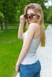 Belle jeune fille sexy sportive mince dans des lunettes de soleil dans le gleet de jeans et d'espadrilles pendant le jour d'été d Images libres de droits