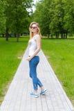 Belle jeune fille sexy sportive mince dans des lunettes de soleil dans le gleet de jeans et d'espadrilles pendant le jour d'été d Photos libres de droits