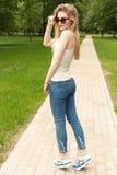 Belle jeune fille sexy sportive mince dans des lunettes de soleil dans le gleet de jeans et d'espadrilles pendant le jour d'été d Image stock
