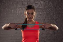 Belle jeune fille sportive s'exerçant avec le caoutchouc élastique, St photo libre de droits
