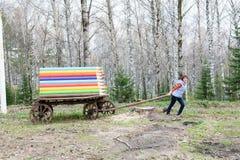 Belle jeune fille tirant un chariot avec les crayons colorés Image libre de droits