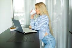 Belle jeune fille travaillant à elle-même avec l'ordinateur portable image libre de droits