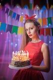 Belle jeune goupille de vintage vers le haut de la fille de style se tenant en gâteau allumé coloré de participation de scène ave Image stock