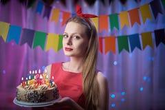 Belle jeune goupille de vintage vers le haut de la fille de style se tenant en gâteau allumé coloré de participation de scène ave Photos stock