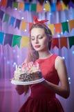 Belle jeune goupille de vintage vers le haut de la fille de style se tenant en gâteau allumé coloré de participation de scène ave Photographie stock libre de droits