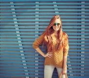 Belle jeune jeune fille rousse dans des lunettes de soleil se tenant près du mur du jour chaud d'été en bois bleu de planches photographie stock libre de droits
