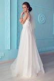 Belle jeune jeune mariée avec les cheveux bouclés sombres dans la robe de mariage luxueuse posant à la pièce photos stock
