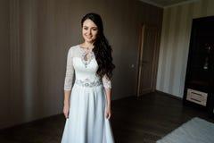 Belle jeune jeune mariée dans la robe blanche attendant le marié à l'intérieur image stock