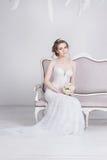 Belle jeune jeune mariée dans une robe de mariage luxueuse de dentelle Elle s'assied sur un sofa blanc de vintage Photos stock