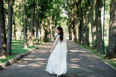 Belle jeune jeune mariée de sourire de brune dans la robe de mariage avec le bouquet des fleurs dans des mains dehors sur le fond Photos libres de droits