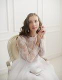 Belle jeune jeune mariée s'asseyant sur une chaise Photo libre de droits