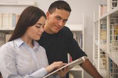 Belle jeune lecture de couples d'université à la bibliothèque ensemble photo libre de droits