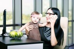 Belle jeune mère avec sa petite fille mignonne dans le bureau Images libres de droits