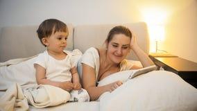Belle jeune mère avec ses 2 années de fils d'enfant en bas âge se situant dans le lit avec le comprimé numérique Images libres de droits