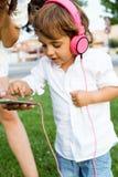 Belle jeune mère avec son fils écoutant la musique en parc Photo stock