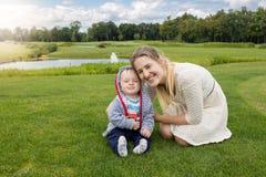 Belle jeune mère et 9 mois gais de relaxi de bébé garçon Photographie stock libre de droits