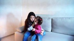 Belle jeune mère et petite fille s'asseyant sur le divan banque de vidéos