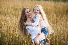 Belle jeune mère et sa fille au champ de blé Photographie stock libre de droits
