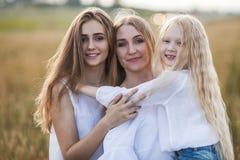 Belle jeune mère et ses filles au champ de blé Images stock