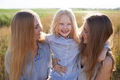 Belle jeune mère et ses filles au champ de blé Photo libre de droits