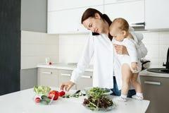 Belle jeune mère faisant cuire le dîner sain, parlant au téléphone et étreignant son petit fils Bébé presque restant sur la table photo stock