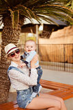 Belle jeune mère un chapeau, lunettes de soleil et shorts tenant un SM Images stock