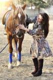 Belle jeune marche femelle et caresse de son cheval brun dans une campagne Photos libres de droits