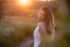 Belle jeune mariée élégante dans une belle danse de robe de mariage sur un coucher du soleil Photo stock