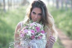 Belle jeune mariée élégante dans une belle robe luxuriante dans la forêt Photos libres de droits