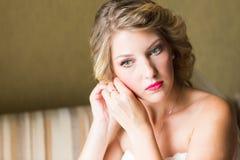 Belle jeune mariée élégante mettant sur le plan rapproché de boucles d'oreille, épousant la préparation Photographie stock libre de droits