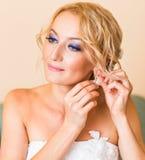 Belle jeune mariée élégante mettant sur le plan rapproché de boucles d'oreille, épousant la préparation Image stock