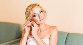 Belle jeune mariée élégante mettant sur le plan rapproché de boucles d'oreille, épousant la préparation Photographie stock