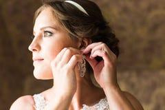 Belle jeune mariée élégante mettant sur le plan rapproché de boucles d'oreille, épousant la préparation Photos stock