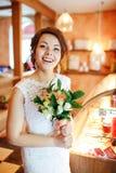 Belle jeune mariée émotive avec le bouquet de mariage dans l'intérieur, visage étonné joyeux, expression du visage Image libre de droits