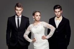 Belle jeune mariée allant choisir entre deux mariés Images libres de droits