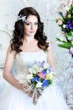 Belle jeune mariée avec des fleurs nous regardant heureusement images stock