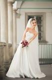 Belle jeune mariée avec le bouquet de mariage posant dans la vieille ville Photographie stock