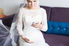 Belle jeune mariée avec le téléphone portable Concept des nouveaux mariés d'amour et d'intérêt Photos libres de droits