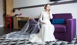 Belle jeune mariée avec le téléphone portable Concept des nouveaux mariés d'amour et d'intérêt Photo libre de droits