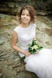 Belle jeune mariée avec les cheveux en désordre sur des pierres parmi des roches, épousant le bouquet dans des mains Portrait fra photographie stock