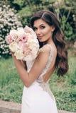 Belle jeune mariée avec les cheveux foncés dans la robe de mariage luxueuse avec le bouquet tendre de mariage photos libres de droits
