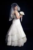 Belle jeune mariée avec un bouquet sur un backgrou noir Photo libre de droits