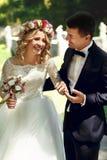 Belle jeune mariée blonde heureuse émotive tenant des mains avec le handso Photographie stock libre de droits