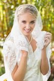 Belle jeune mariée blonde tenant son voile regardant l'appareil-photo heureusement Image stock