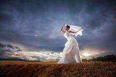 Belle jeune mariée dans la forêt, ciel bleu crépusculaire nuageux Photographie stock libre de droits