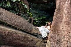 belle jeune mariée dans la robe blanche se reposant sur le grand arbre et posant pour épouser images stock